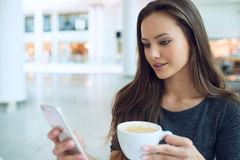 Kvinna med koppen kaffe i restaurangen som stannar till mobiltelefonen arkivbilder