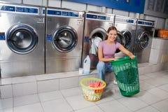 Kvinna med korgar av kläder på tvätterit Arkivbild