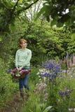 Kvinna med korgen av blommor i trädgård Royaltyfri Fotografi