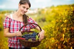 Kvinna med korgen som är full av druvor arkivbild