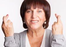Kvinna med korsade fingrar Arkivfoto