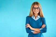 Kvinna med korsade händer på blå bakgrund fotografering för bildbyråer