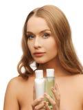 Kvinna med kosmetiska flaskor Royaltyfria Bilder
