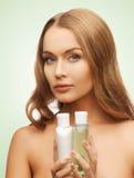 Kvinna med kosmetiska flaskor Arkivfoto
