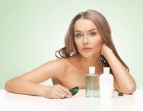 Kvinna med kosmetiska flaskor Arkivfoton