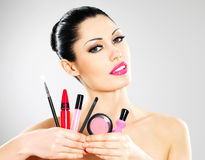 Kvinna med kosmetiska hjälpmedel för makeup nära henne framsida. Fotografering för Bildbyråer
