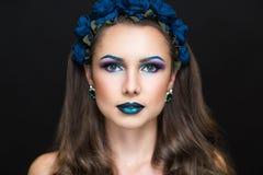 Kvinna med kransen av blåa rosor Arkivfoton