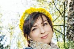 Kvinna med kransen av maskrosor i parkera Arkivfoto