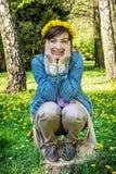 Kvinna med kransen av maskrosor i parkera Royaltyfri Fotografi
