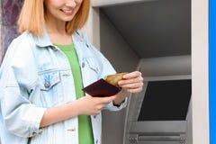 Kvinna med kreditkorten nära bankomaten, closeup arkivfoton