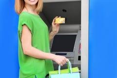 Kvinna med kreditkorten nära bankomaten, closeup fotografering för bildbyråer