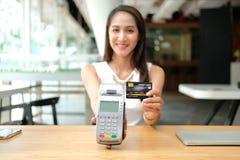 Kvinna med kreditkorten som nallar maskinen shoppa livsstil & betalning med nfcteknologi royaltyfria bilder