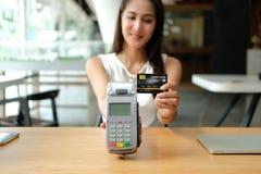 Kvinna med kreditkorten som nallar maskinen shoppa livsstil & betalning med nfcteknologi royaltyfria foton