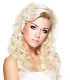 Kvinna med långt blont lockigt hår Arkivfoto
