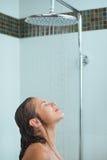 Kvinna med långt hår som tar duschen under vattenstrålen Arkivbilder