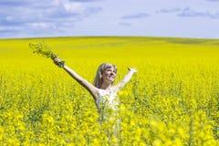 Kvinna med långt håranseende på gul rapsfröäng med lyftta händer Begrepp av frihet och lycka Arkivbild