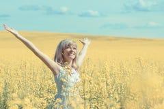 Kvinna med långt håranseende på gul rapsfröäng med lyftta händer Begrepp av frihet och lycka Fotografering för Bildbyråer