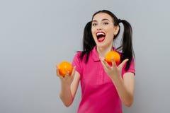 Kvinna med långt rakt hår och att rymma två apelsiner som upp ser grå bakgrund Royaltyfri Fotografi