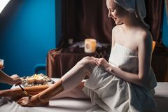 Kvinna med leramaskeringen på ben som kopplar av i brunnsortsalong royaltyfria bilder