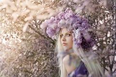 Kvinna med lila blommor Royaltyfria Foton