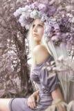 Kvinna med lila blommor Royaltyfria Bilder