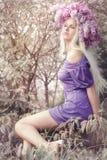 Kvinna med lila blommor Arkivfoto
