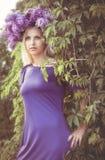 Kvinna med lila blommor Fotografering för Bildbyråer