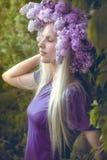 Kvinna med lila blommor Arkivbild