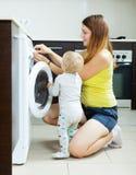 Kvinna med lilla barnet som använder tvagningmaskinen Royaltyfri Foto
