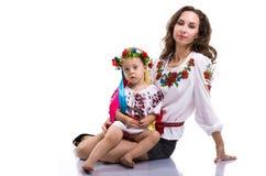 Kvinna med lite flickan i den ukrainska medborgarekläderna royaltyfria foton