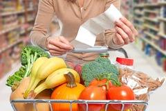 Kvinna med livsmedelsbutikkvittot och shoppingvagnen Arkivfoto