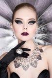 Kvinna med ljus makeup och med uppsättningsmycken Fotografering för Bildbyråer