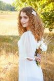 Kvinna med lockigt guld- hår som ler att stå i fältet Arkivfoto