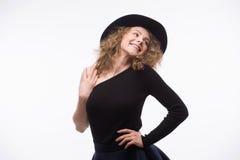 Kvinna med lockigt hår i svart hatt och stilfull elegant aftonklänning arkivbilder