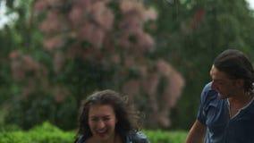 Kvinna med lockigt vått hår som talar till hennes pojkvän och skratta Den skämtsamma parspringen i regnet stock video