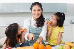 Kvinna med lyckliga två döttrar som klipper frukt i kök Royaltyfria Foton