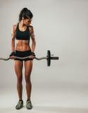 Kvinna med lyftande skivstången för muskulös fysik royaltyfri bild