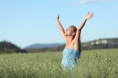 Kvinna med lyftta armar i en grön äng som tycker om vinden Arkivbild