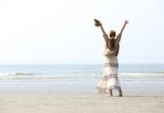 Kvinna med lyftta armar på stranden Royaltyfri Foto