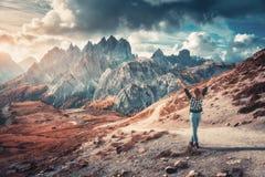 Kvinna med lyftta upp armar och höga berg på solnedgången arkivfoto