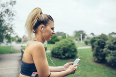 Kvinna med lyssnande musik för hörlurar i smartphone Arkivbild