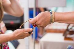 Kvinna med lyxiga gemstonecirklar och armband som säljer dyra smycken royaltyfri foto