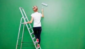 Kvinna med målarfärgrullen och stege i eget hus arkivbild