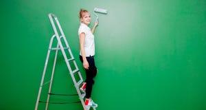 Kvinna med målarfärgrullen och stege i eget hus royaltyfria foton