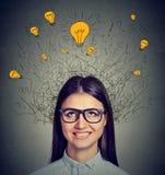 Kvinna med många ljusa kulor för idéer ovanför huvudet som ser upp Arkivbilder