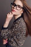 Kvinna med mörkt hår i elegant leopardtryckskjorta och med exponeringsglas Arkivbilder