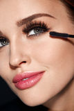 Kvinna med makeup, långa ögonfrans som applicerar mascara Göra makeup arkivfoto