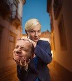 Kvinna med mans huvud i hennes hand arkivfoto
