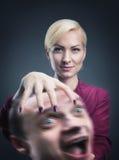 Kvinna med mans huvud i hennes hand arkivfoton