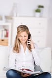 Kvinna med mappen genom att använda telefonen hemma Arkivfoto